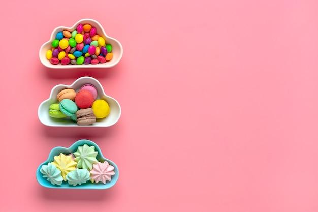 Bonbons colorés - sucettes, meringues, macaron dans un bol en forme de nuage isolé sur rose