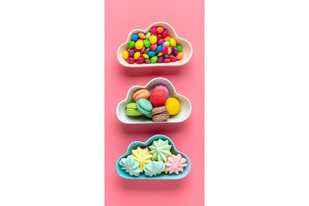 Bonbons colorés - sucettes, meringues, macaron dans un bol en forme de nuage