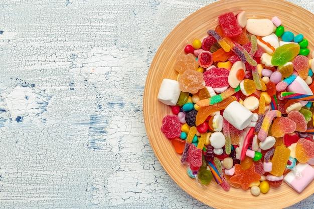Bonbons colorés sur une table en bois.