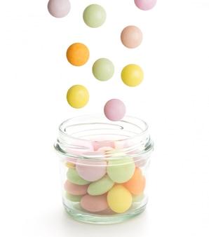 Bonbons colorés tombant dans le pot isolé sur fond blanc.