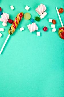 Bonbons colorés sur turquoise pastel.