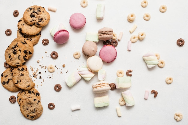 Bonbons colorés sur la vue de dessus de fond blanc. scone au chocolat complet, macarons et guimauve comme art culinaire de la pâtisserie maison, concept de boulangerie sucrée
