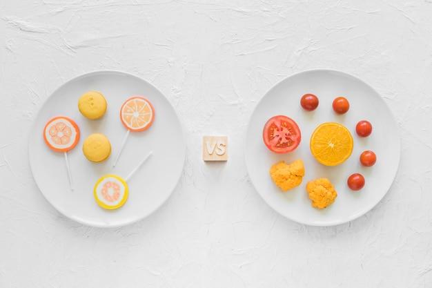 Bonbons contre des légumes sains sur une plaque blanche sur fond texturé