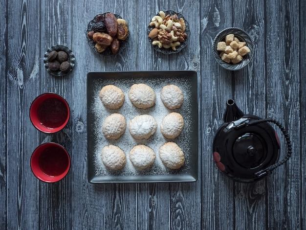 Des bonbons du ramadan faits à la main sont servis avec du thé sur la table. biscuits égyptiens