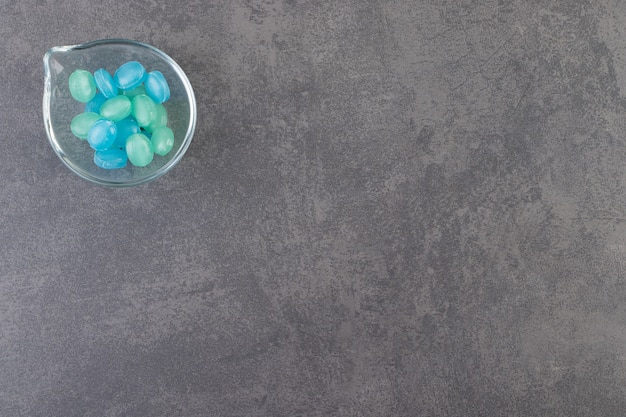 Bonbons durs bleus et verts dans un bol placé sur une table en pierre.