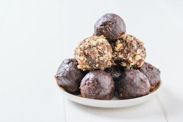 Bonbons faits maison à base de noix, fruits secs, chocolat et miel sur une assiette sur une table blanche et une barre de chocolat.