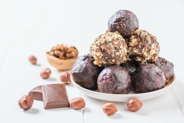Bonbons faits maison à base de noix, fruits secs, chocolat et miel sur une assiette sur une table blanche et noix.