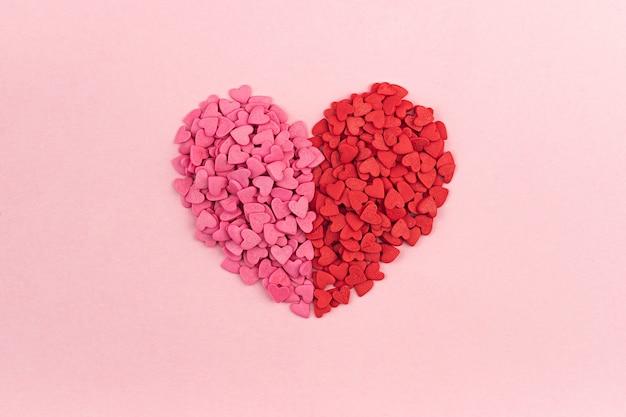 Bonbons en forme de coeur rose et rouge saint valentin sur un fond pastel.texture de coeurs vue de dessus plat poser. concept d'amour sainte valentine, cartes de voeux de fête des mères, invitation.
