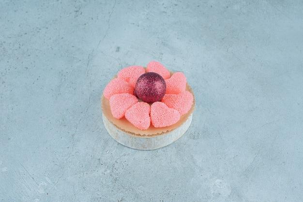 Bonbons en forme de coeur en sucre avec boule de noël brillante.