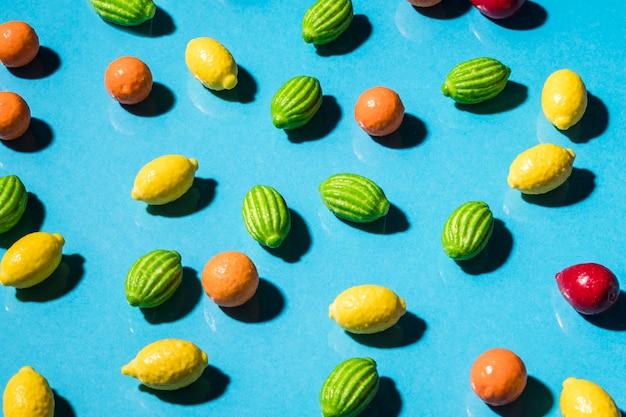 Bonbons en forme de fruits sur la toile de fond bleue