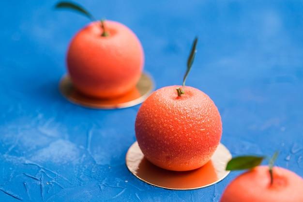 Bonbons, gâteaux et délicieux concept - mousse dessert en forme de fruit orange.