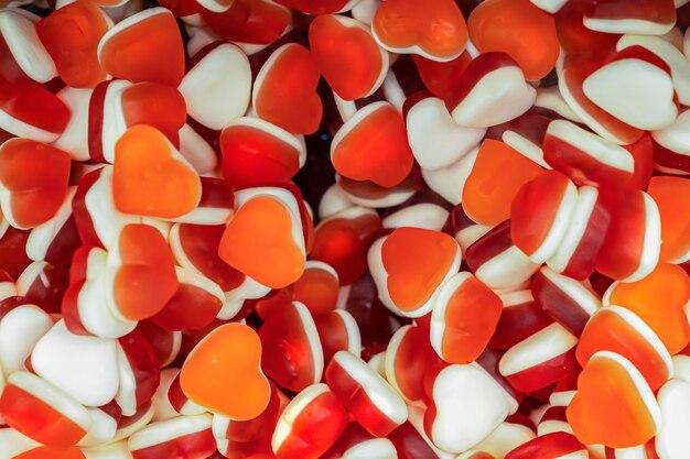 Bonbons de gelée bonbons en forme de coeur saint valentin, fond de texture romantique rougeâtre pour la mise en page et la carte postale. couleurs rouge et blanc