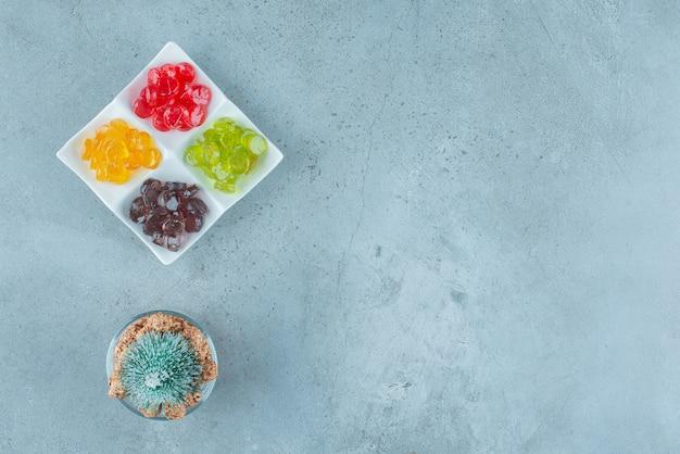 Bonbons à la gelée colorés avec un arbre de noël sur marbre.