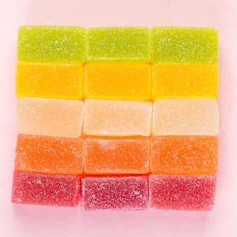 Bonbons à la gelée colorés formant une forme carrée sur une surface rose