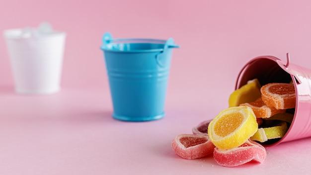 Bonbons de gelée de fruits colorés dans un seau rose