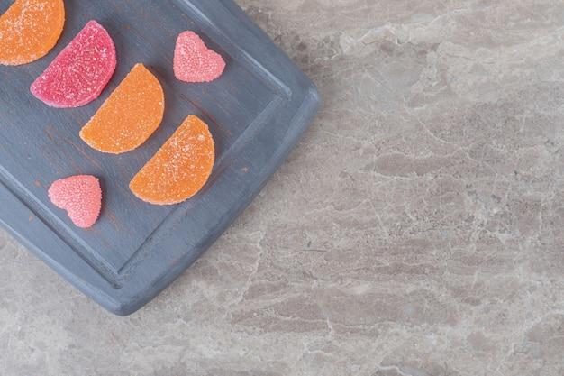 Bonbons à la gelée soigneusement disposés sur un tableau marine sur une surface en marbre