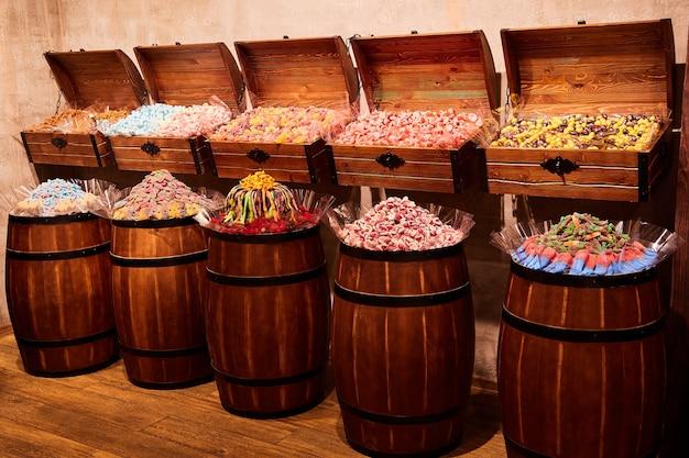 Des bonbons gélifiés multicolores et des guimauves sont vendus dans le magasin dans des tonneaux et des coffres en bois