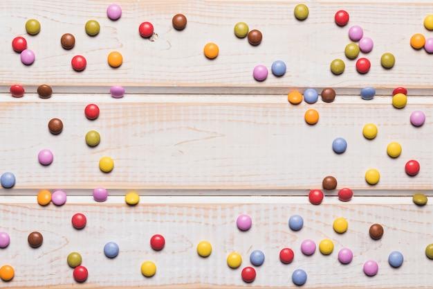 Bonbons gem répartis sur le bureau en bois avec un espace au centre