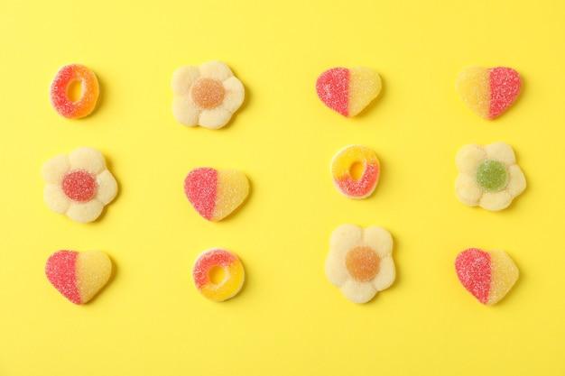 Bonbons gommeux sur fond jaune, vue de dessus.