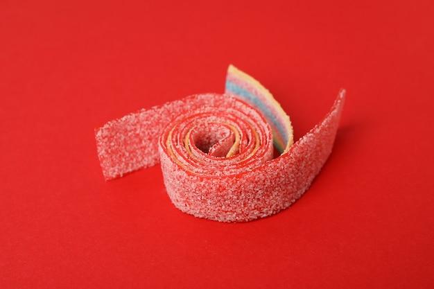 Bonbons gommeux sur fond rouge, gros plan.