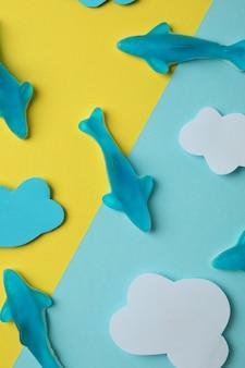Bonbons gommeux en forme de baleine et nuages décoratifs sur fond bicolore.