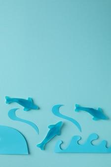 Bonbons gommeux en forme de baleine et vagues décoratives sur fond bleu.