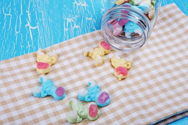 Bonbons gommeux de vache colorés dispersés dans un bocal en verre