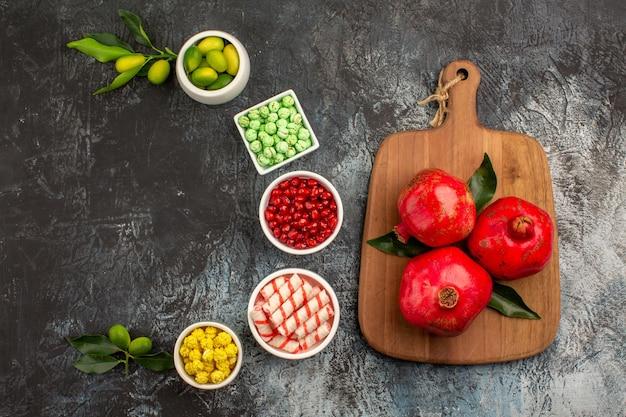 Bonbons grenades rouges sur la planche de cuisine graines de grenade limes bonbons