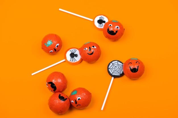 Bonbons d'halloween avec des araignées noires, citrouilles souriantes et toile d'araignée sur fond orange, vue de dessus
