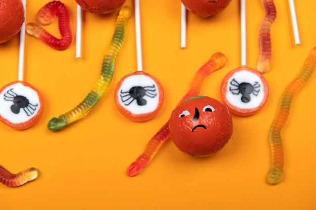 Bonbons d'halloween avec araignées noires, toile d'araignée, citrouille et vers de gelée savoureux sur fond orange, vue de dessus