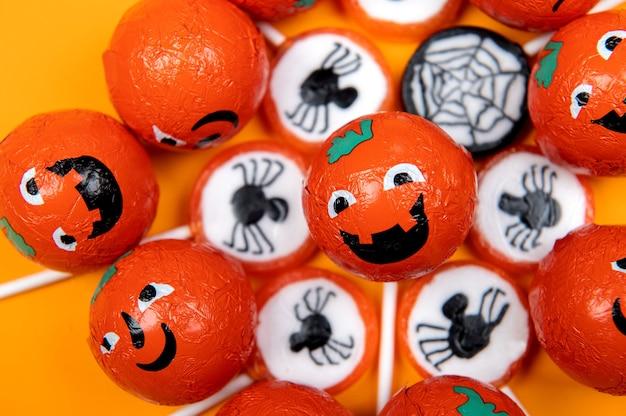 Bonbons d'halloween avec des araignées noires, toile d'araignée, citrouilles souriantes et en colère sur fond orange, vue de dessus