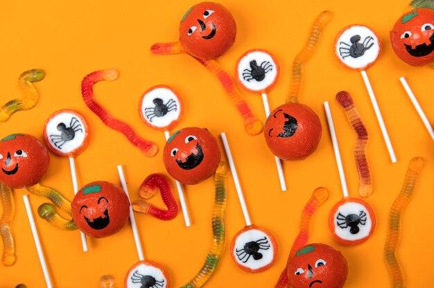 Bonbons d'halloween avec des araignées noires, une toile d'araignée, des citrouilles souriantes et de savoureux vers de gelée sur fond orange, vue de dessus