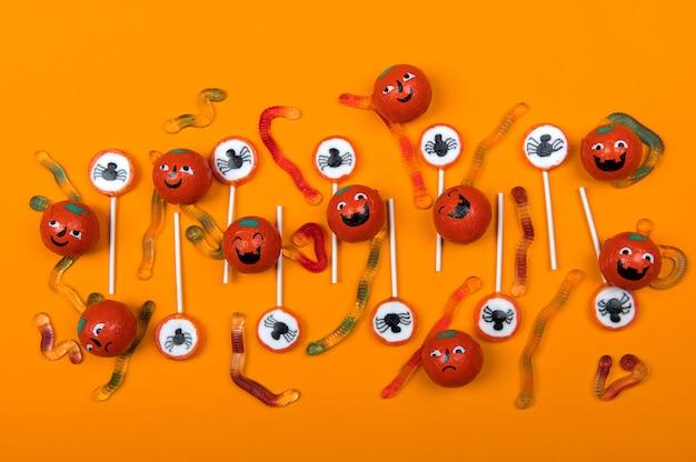 Bonbons d'halloween avec des araignées noires, une toile d'araignée, des citrouilles souriantes et des vers de gelée sur fond de couleur orange, vue de dessus