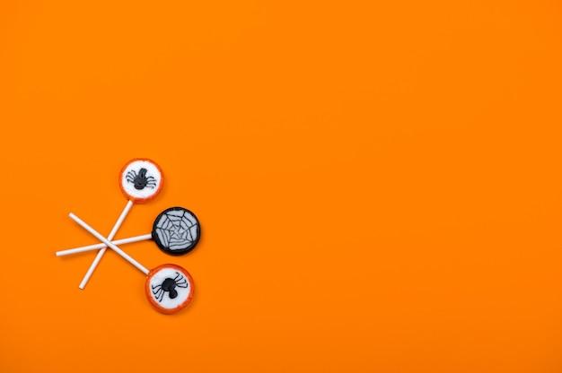 Bonbons d'halloween avec des araignées noires et une toile d'araignée sur fond de couleur orange, vue de dessus