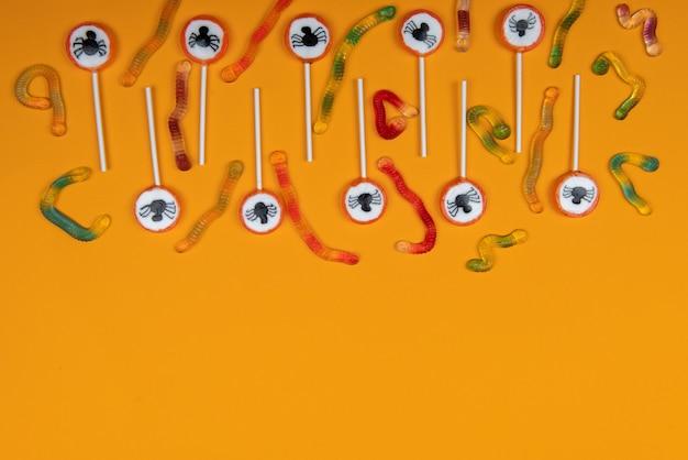 Bonbons d'halloween avec des araignées noires, une toile d'araignée et de savoureux vers de gelée sur fond de couleur orange, vue de dessus