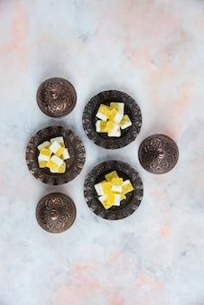 Bonbons jaunes sur la vaisselle sur une surface blanche