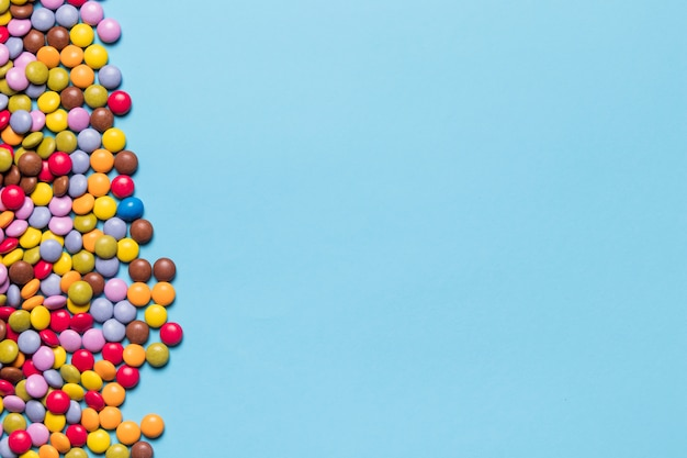 Bonbons joyaux colorés sur le côté de fond bleu