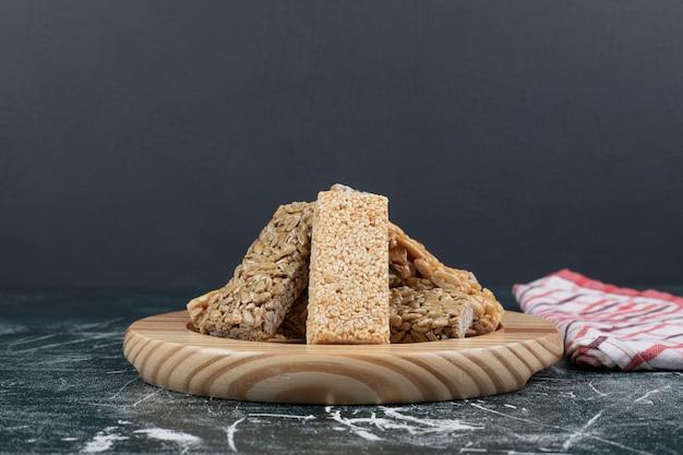 Bonbons kozinaki avec graines et noix sur plaque en bois. photo de haute qualité