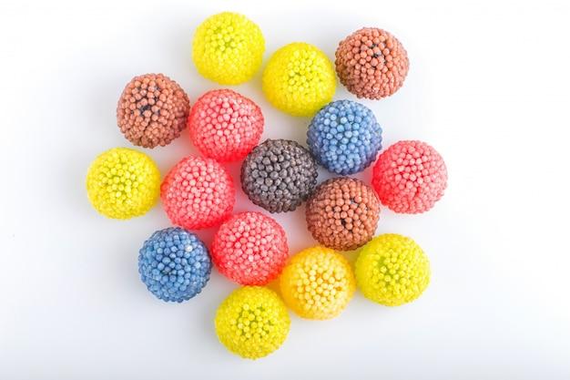 Bonbons à mâcher multicolores colorés sous la forme de framboises isolés sur blanc.