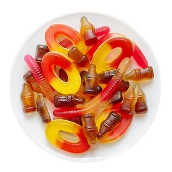 Bonbons à mâcher sous forme de cola, vers, loopies sur la plaque isolée sur fond blanc. vue de dessus.