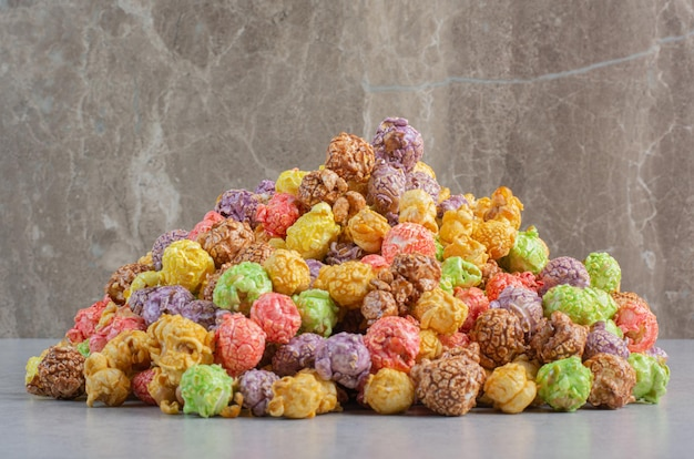 Bonbons de maïs soufflé colorés empilés sur une surface en marbre