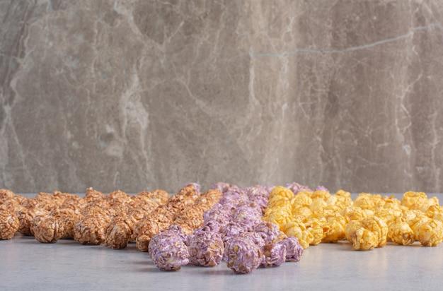 Bonbons de maïs soufflé de couleur alignés sur du marbre.