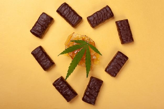 Bonbons à la marijuana, coeur composé de chocolats avec une feuille de cannabis médical et d'huile de marijuana sur fond jaune.