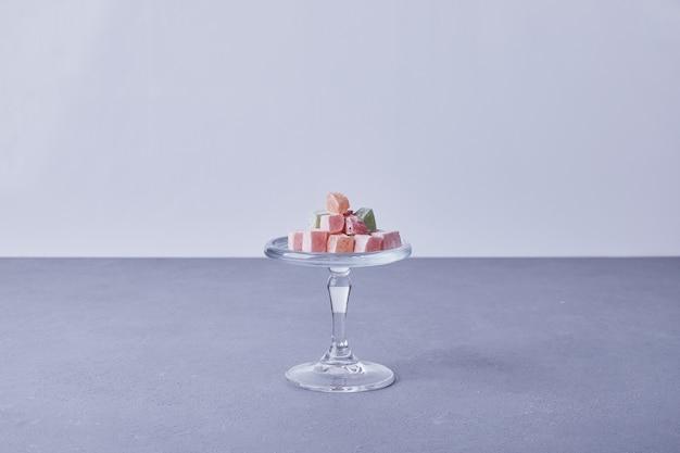 Bonbons à la marmelade dans une tasse en verre au centre sur bleu.
