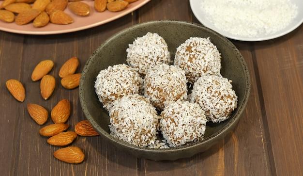 Bonbons de massepain étant recouverts de noix de coco râpée sur une surface en bois.