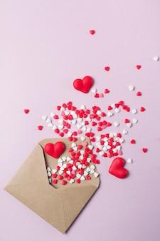 Bonbons multicolores bonbons au sucre coeurs volent hors de l'enveloppe postale en papier kraft. concept de la saint-valentin heureux. contexte festif