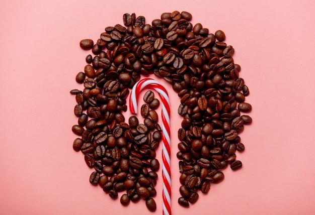 Bonbons de noël et grains de café sur mur rose