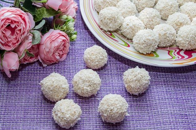 Bonbons de noix de coco faits maison sur un espace de fleurs roses. bonbons pour la saint valentin.
