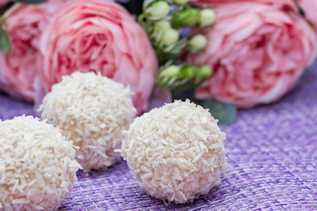 Bonbons à la noix de coco faits maison sur fond de fleurs roses. bonbons pour la saint-valentin.