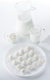 Bonbons à la noix de coco sur fond d'une cruche et d'une tasse de lait et de bols de fromage cottage